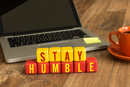 modesty: Stay humble written on a wooden cube with laptop background