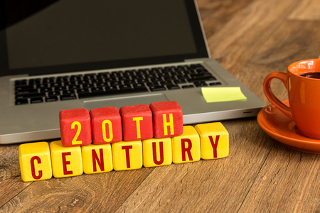 20th century: 20th century written on a wooden cube with laptop background Stock Photo