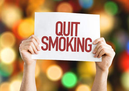 Hands holding cardboard on bokeh background with text: Quit smoking Stock Photo