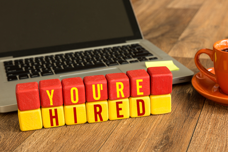Youre hired written on a wooden cube with laptop background Stock Photo