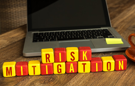 mitigation: Risk mitigation written on a wooden cube with laptop background Stock Photo