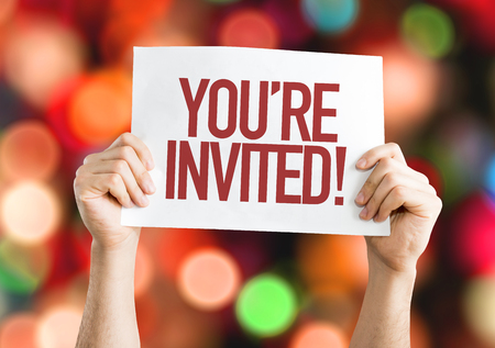 Hands holding cardboard on bokeh background with text: You're invited! Stock Photo - 64839736