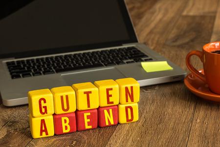 good evening: Guten abend (Good evening in German) written on a wooden cube with laptop background