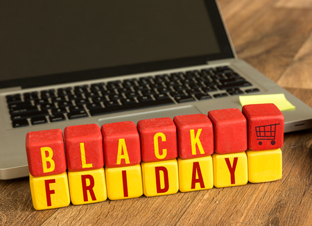 Black Friday written on a wooden cube with laptop background