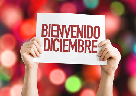 bienvenido: Hands holding cardboard on bokeh background with text: Bienvenido Diciembre (Welcome December in Spanish)