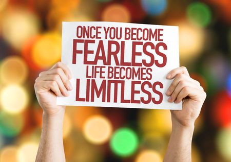 unafraid: Hands holding cardboard on bokeh background with text: Once you become fearless life becomes limitless Stock Photo