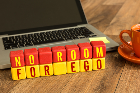 selfish: No room for ego written on a wooden cube with laptop background Stock Photo