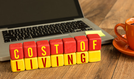 Cost of living written on a wooden cube with laptop background Stock Photo