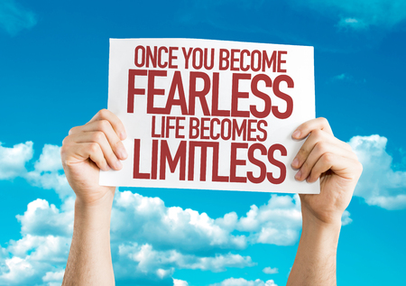 unafraid: Hands holding cardboard on sky background with text: Once you become fearlesslife becomes limitless Stock Photo