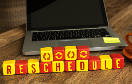 rescheduling: Reschedule written on a wooden cube with laptop background