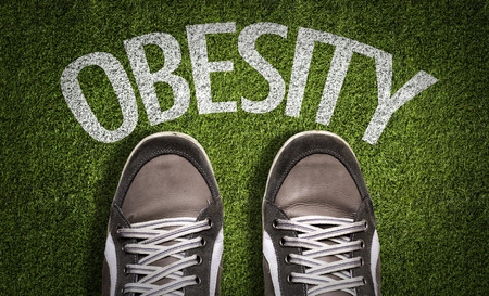 Text on field with shoes background: Obesity Stock Photo
