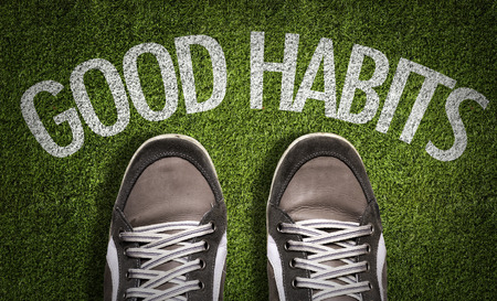 Text on field with shoes background: Good habits Stock Photo