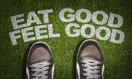 Text on field with shoes background: Eat good feel good Stock Photo