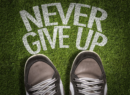 Text on field with shoes background: Never give up