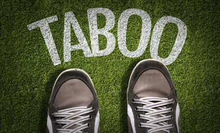 Text on field with shoes background: Taboo Stock Photo