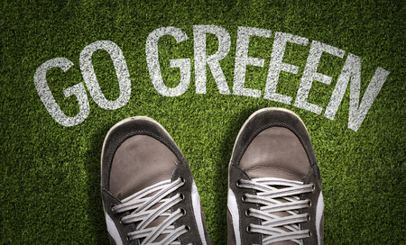 go green background: Text on field with shoes background: Go green Stock Photo