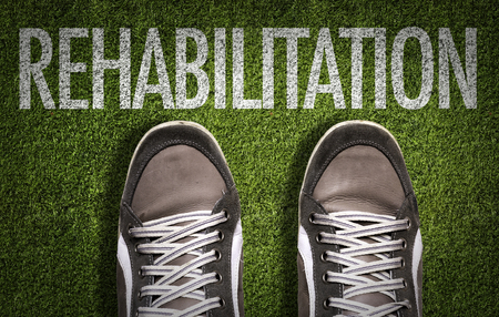 Text on field with shoes background: Rehabilitation