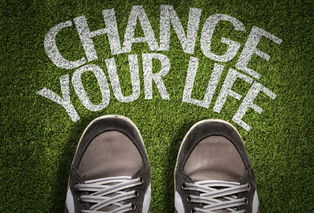 Text on field with shoes background: Change your life Stock Photo