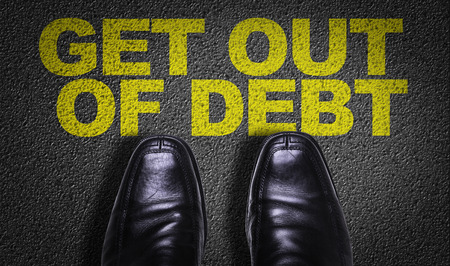 debt goals: Text on road with business shoes background: Get out of debt