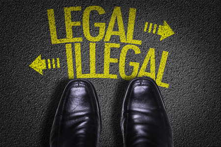 law enforcing: Text on road with business shoes background: LegalIllegal
