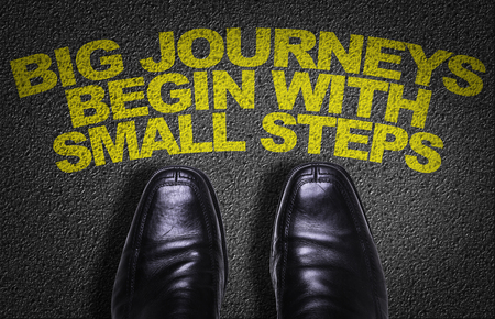 achieve: Text on road with business shoes background: Big journeys begin with small steps