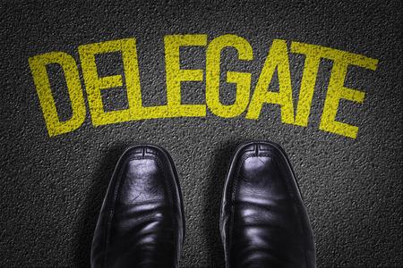 delegar: Texto en el camino con los zapatos del negocio de fondo: Delegado