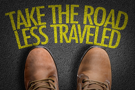 travelled: Text on road with boots background: Take the road less travelled
