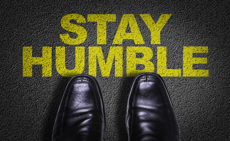 Text on road with business shoes background: Stay humble