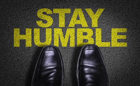 Texto en el camino con los zapatos del negocio de fondo: Manténgase humilde Foto de archivo - 65024874