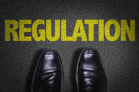 regulators: Text on road with business shoes background: Regulation