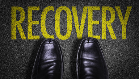 road to recovery: Text on road with business shoes background: Recovery