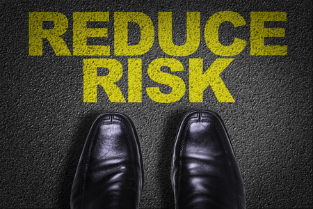 reduce risk: Text on road with business shoes background: Reduce risk Stock Photo