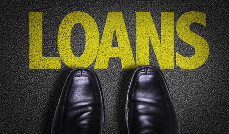 loans: Text on road with business shoes background: Loans Stock Photo
