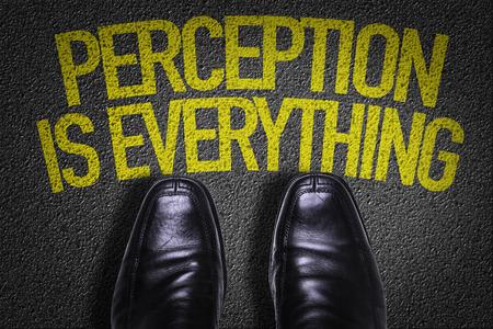 Texto en la carretera con fondo de zapatos de negocios: la percepción es todo Foto de archivo