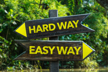difficult lives: Hard wayEasy way sign with wetland background