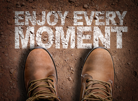 Text on road with boots background: Enjoy every moment