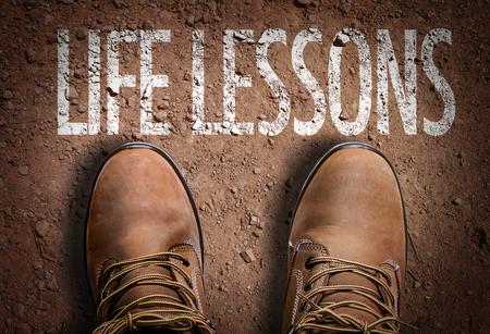 Texto en el camino con botas de fondo: Lecciones de vida