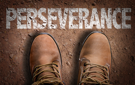 persistence: Text on road with boots background: Perseverance Stock Photo
