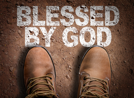 Text on road with boots background: Blessed by God