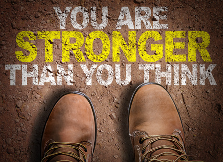 Text on road with boots background: You are stronger than you think Stock Photo