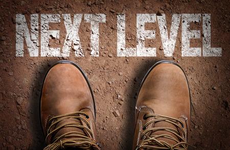 Tekst op de weg met laarzen achtergrond: Next level