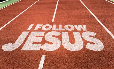 나는 달리기 선로 배경에 쓰여진 예수를 따른다. 스톡 콘텐츠