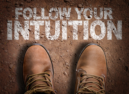 instinct: Text on road with boots background: Follow your intuition Stock Photo