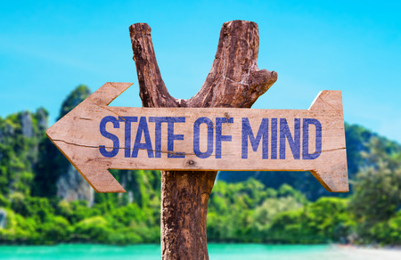 Wooden sign board in wetland with text: State of mind