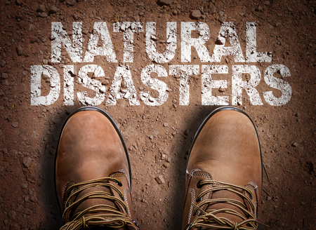 natural disasters: Text on road with boots background: Natural disasters Stock Photo