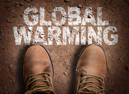 climate change: Text on road with boots background: Global warming