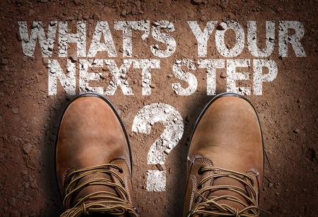 Texto en el camino con botas de fondo: ¿Cuál es su próximo paso? Foto de archivo