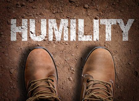 humility: Texto en el camino con botas de fondo: Humildad Foto de archivo