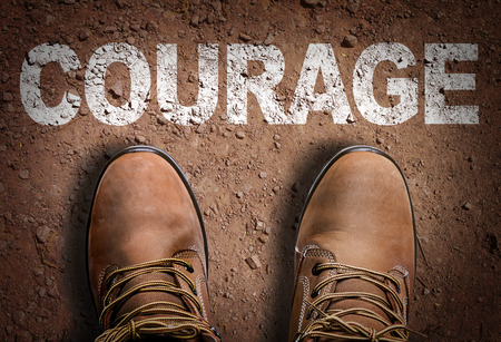 unafraid: Text on road with boots background: Courage