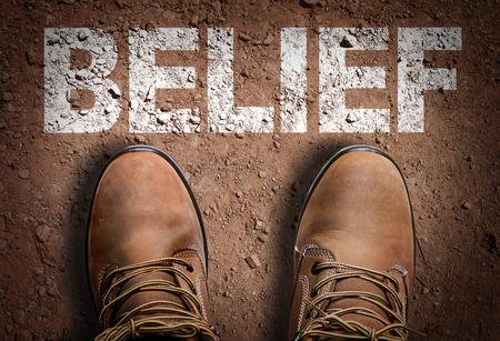 Tekst op de weg met laarzen achtergrond: Geloof